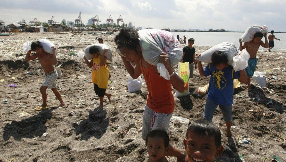 Varias personas transportan sacos en Filipinas para impedir el paso del agua