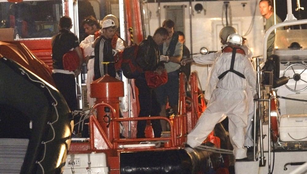 Miembros de Salvamento Marítimo ayudan a desembarcar a varios inmigrantes