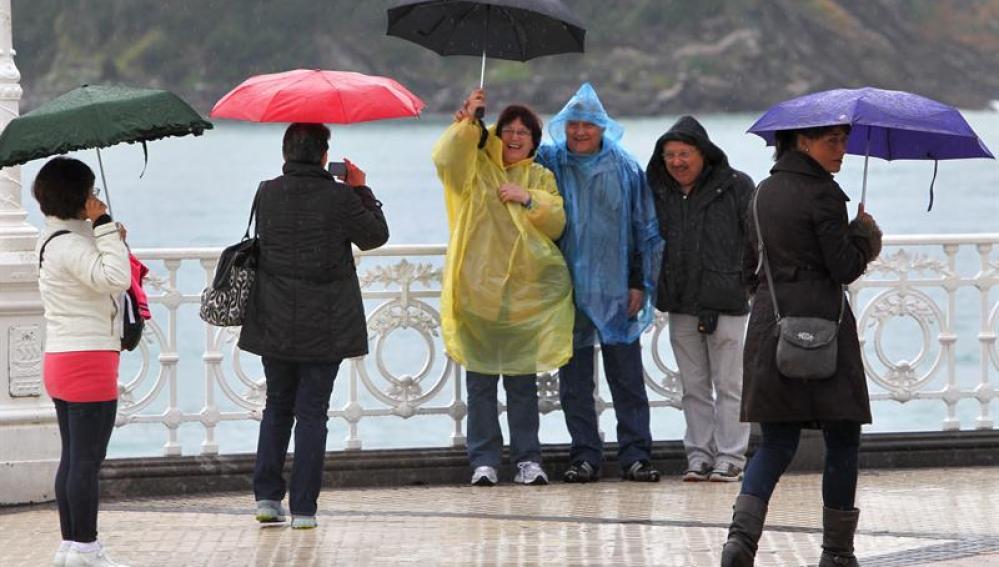 Un grupo de turistas se fotografía frente al mar, en el Paseo de la Concha de San Sebastián