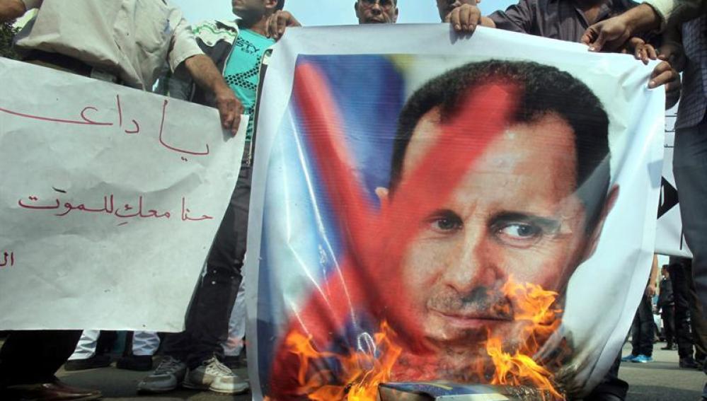 Manifestantes queman una pancarta con la fotografía del presidente sirio, Bachar al Asad
