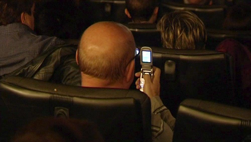 Un hombre mira su móvil en un cine