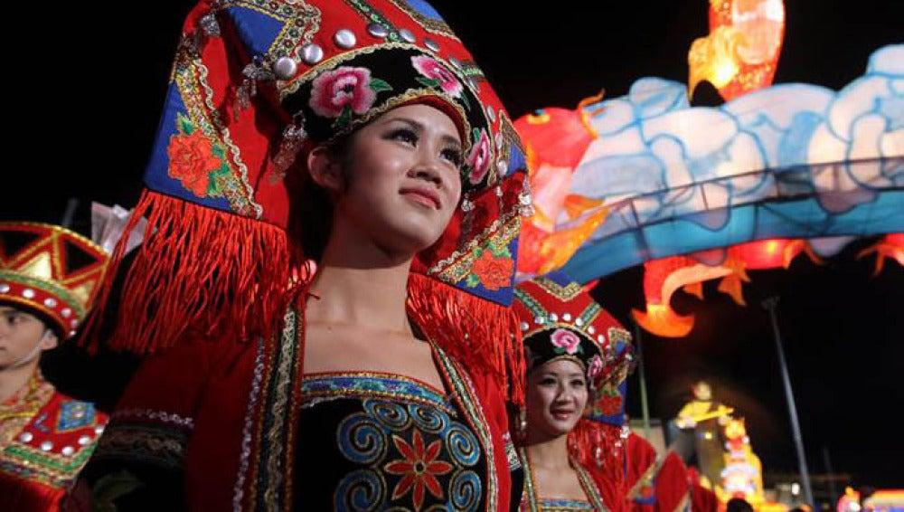 Una mujer con el traje tradicional da la bienvenida a las celebraciones de la víspera