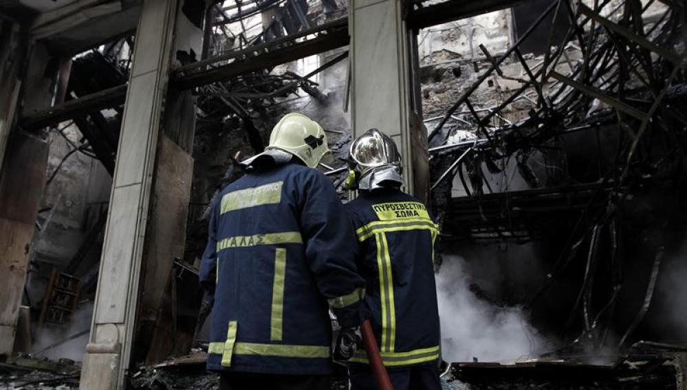 Bomberos apagando los restos del fuego nocturno