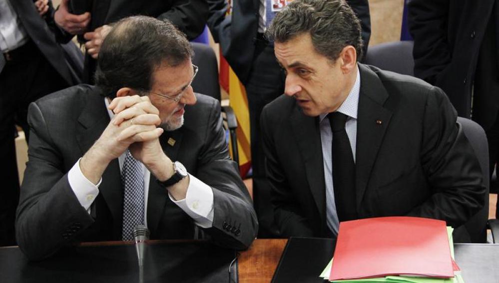El primer ministro español, Mariano Rajoy (i), charla con el presidente francés, Nicolas Sarkozy