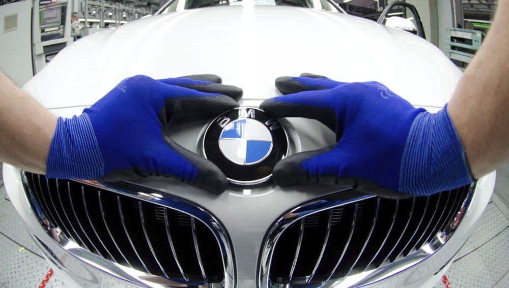 Un empleado coloca la insignia de BMW en un vehículo