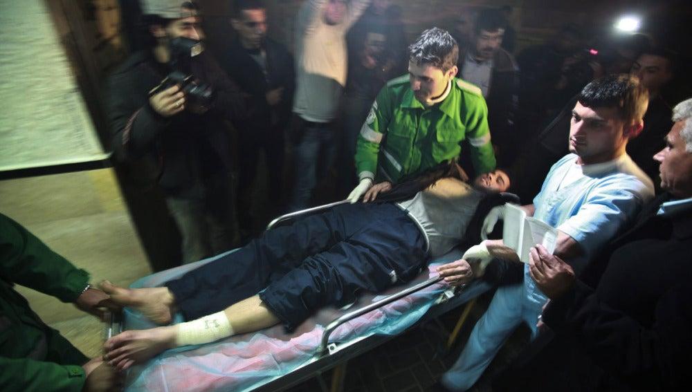 Sanitarios trasladan a un herido en un bombardeo en Gaza