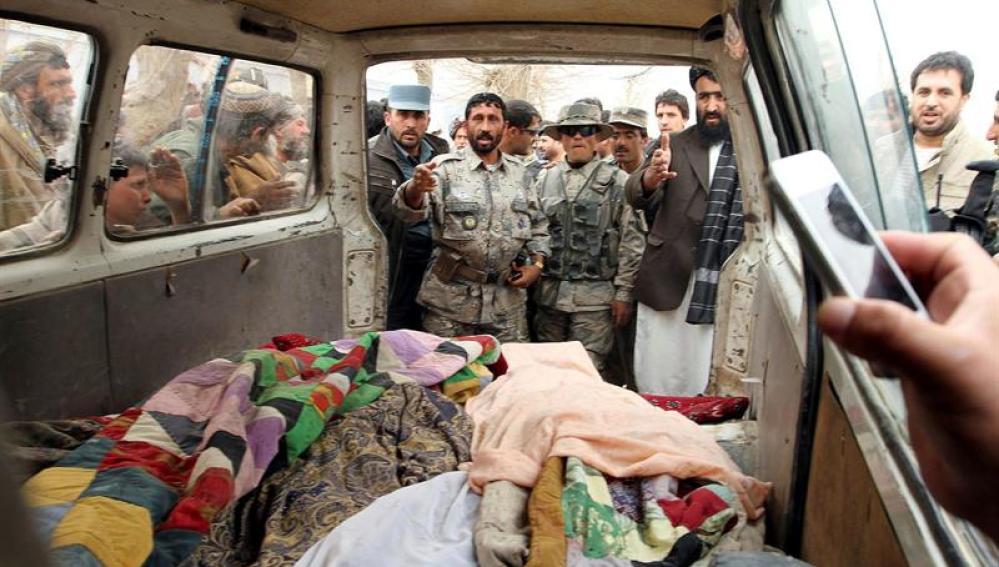Personas muestran los cadáveres de afganos asesinados presuntamente por un soldado estadounidense
