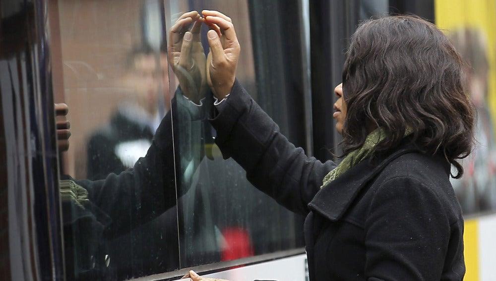 Una mujer permanece junto a uno de los autobuses