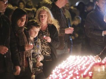 Unas personas encienden velas durante una misa al aire libre frente a la iglesia de Saint Joseph