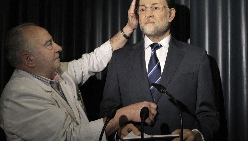 Un técnico del Museo de Cera da los últimos retoques a la figura de Rajoy