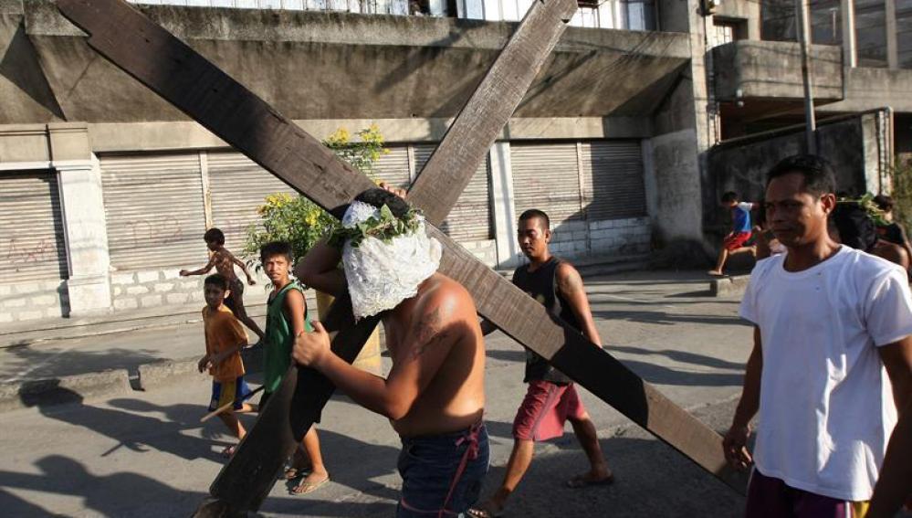 Un penitente filipino porta una gran cruz en una calle de la ciudad de San Fernando, Filipinas