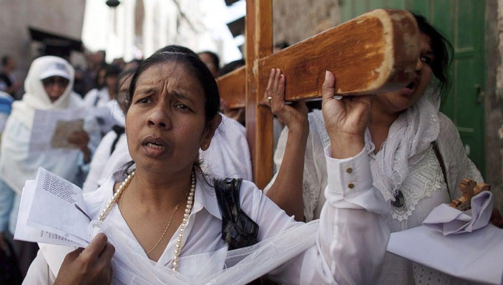 Varios peregrinos portan una cruz mientras participan en el Vía Crucis