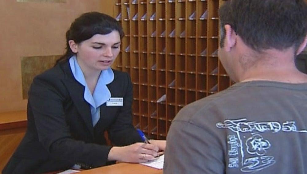 Una recepcionista atiende a un cliente