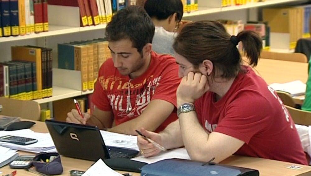 Dos jóvenes estudian en una biblioteca