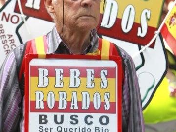 Un hombre porta un cartel con datos para la búsqueda de un familiar