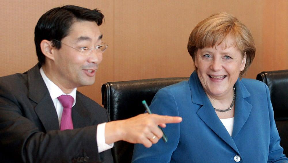 Angela Merkel conversa con el ministro de Economía, Philipp Rösler