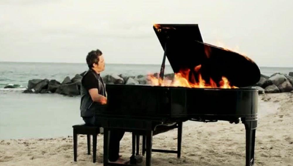 Alejandro Sanz toca un piano en llamas en la playa.