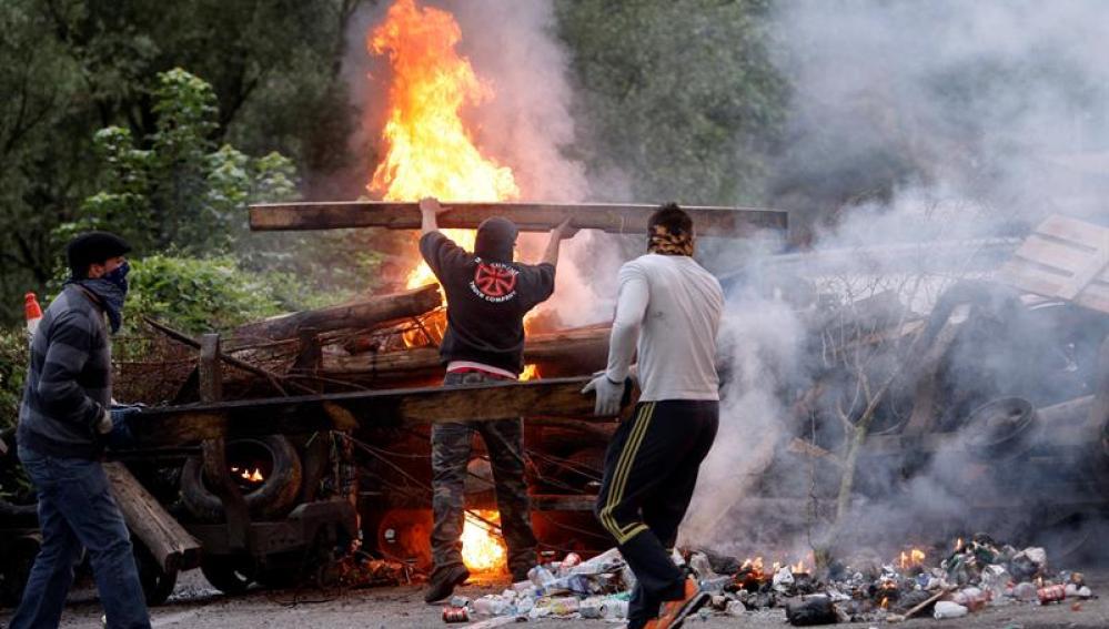 Varios mineros cortan una carretera con una barricada