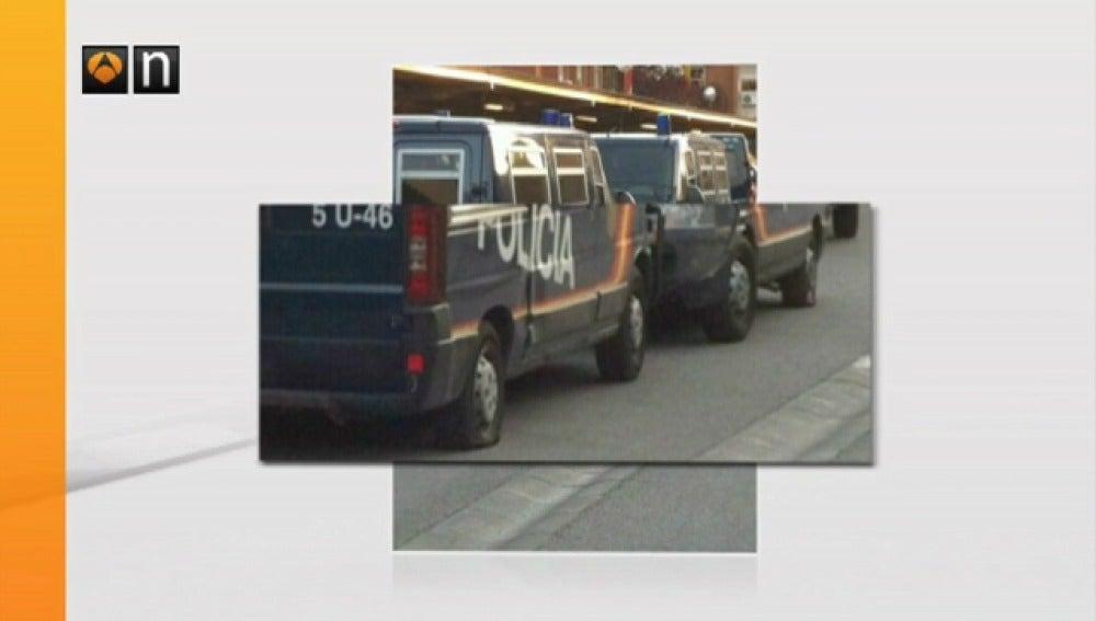 Furgones policiales con las ruedas pinchadas