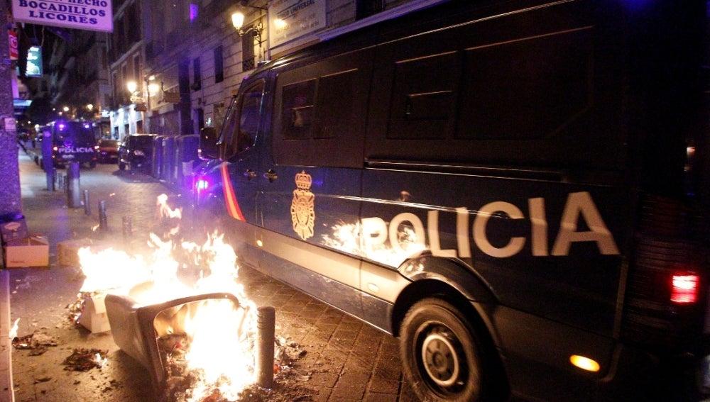 Dos furgones de la Policía Nacional junto a cubos de basura ardiendo