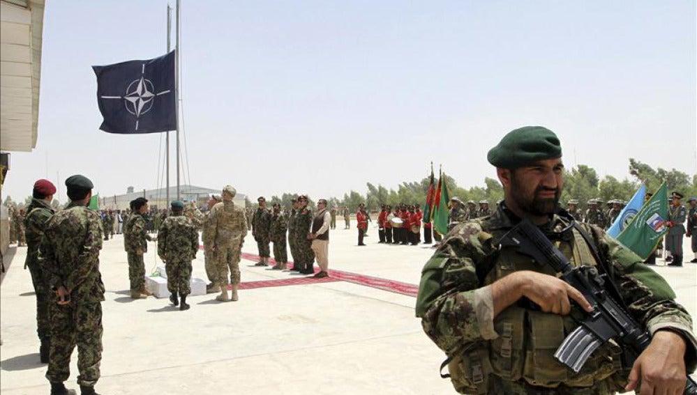 Soldados en Afganistán con la bandera de la OTAN al fondo