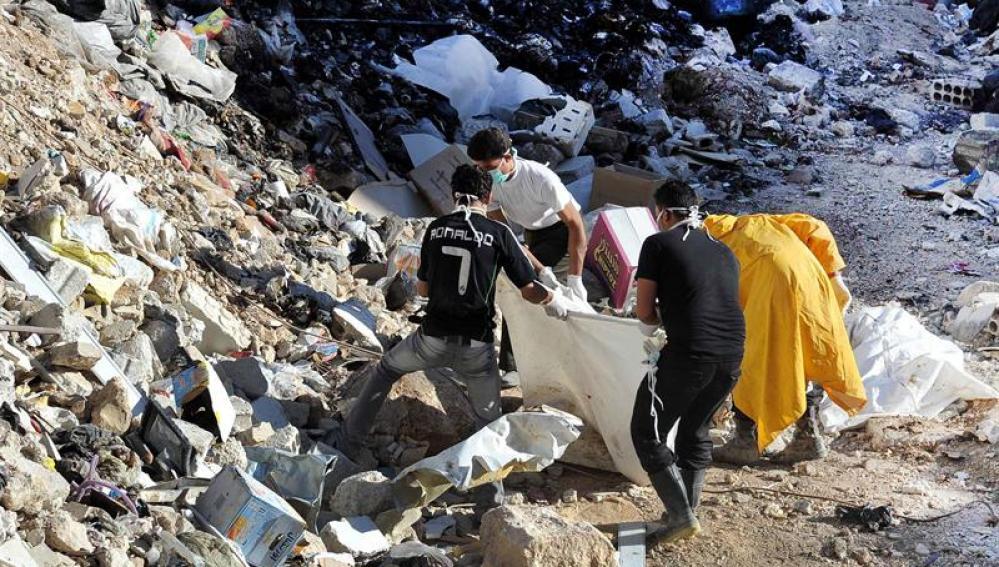 Personas llevan cuerpos mutilados a un cementerio en el área de Yalda, 10 kilómetros al sur de Damasco