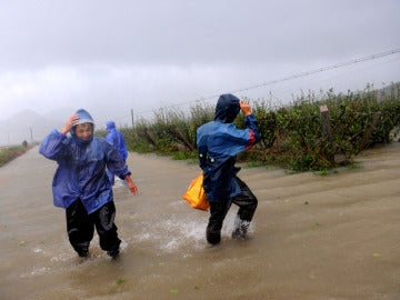 Granjeros intentan proteger sus estanques en una granja acuática inundada