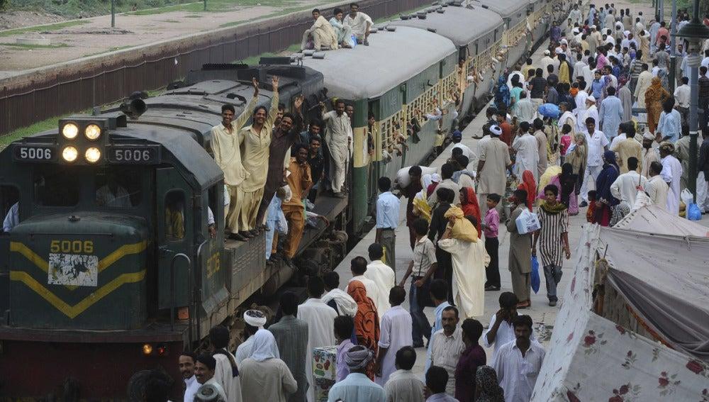 Varias personas se suben a un tren para acudir a la festividad religiosa del 'Aid el Fitr' en Pakistán