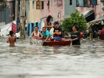 Filipinos atraviesan una calle inundada de Manila