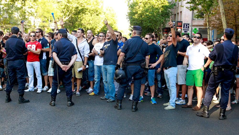 Funcionarios ante la sede del PP, en Madrid, frente a unos agentes de la Policía