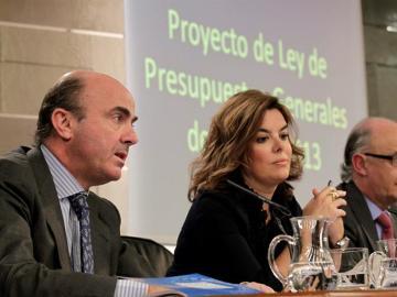 El ministro de Economía, Luis de Guindos, junto a la vicepresidenta del Gobierno, Soraya Sáenz de Santamaría, y el titular de Hacienda y Administraciones Públicas, Cristóbal Montoro
