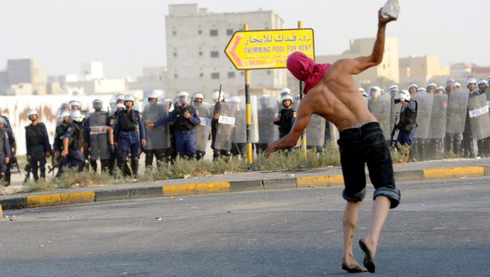 Un manifestante lanza un objeto a la policía