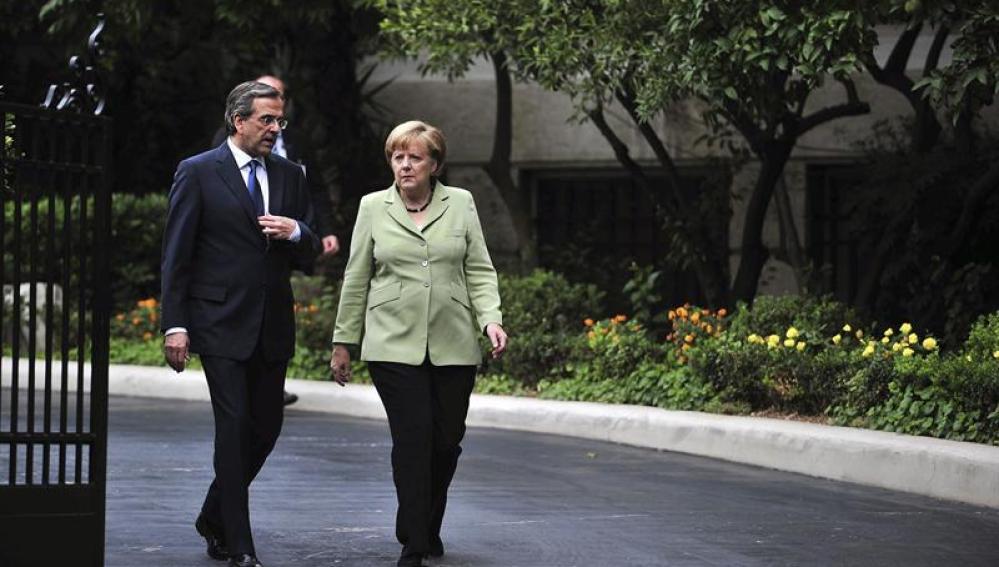 El primer ministro Griego, Andonis Samarás, camina junto a la canciller alemana, Angela Merkel