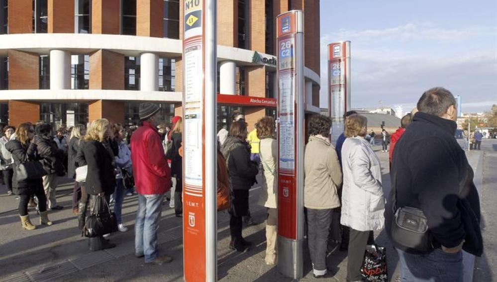 Personas en la parada del autobús durante la jornada de huelga.