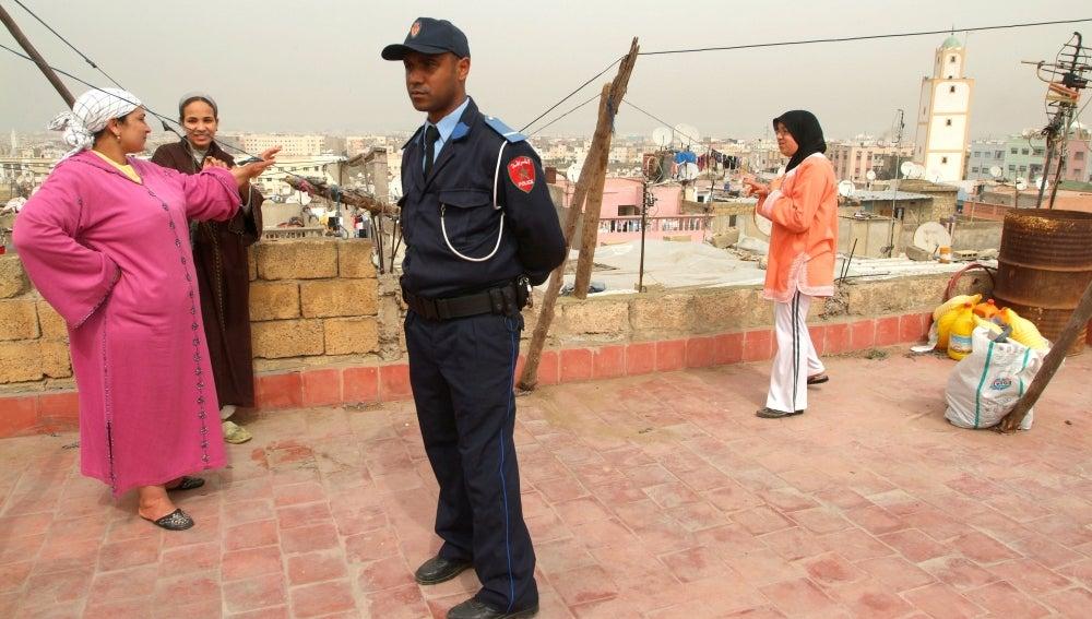 Un agente de la policía marroquí permanece junto a unas mujeres en el barrio de Mulay Rachid, de Casablanca (Marruecos)