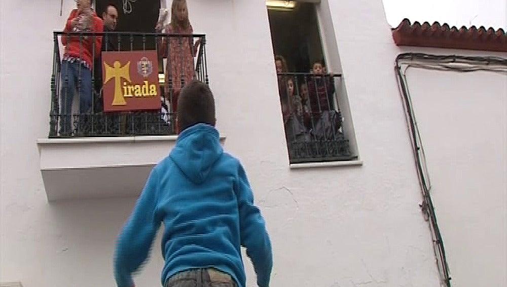 Vecinos de Trigueros intentando coger la comida que le tiran al santo