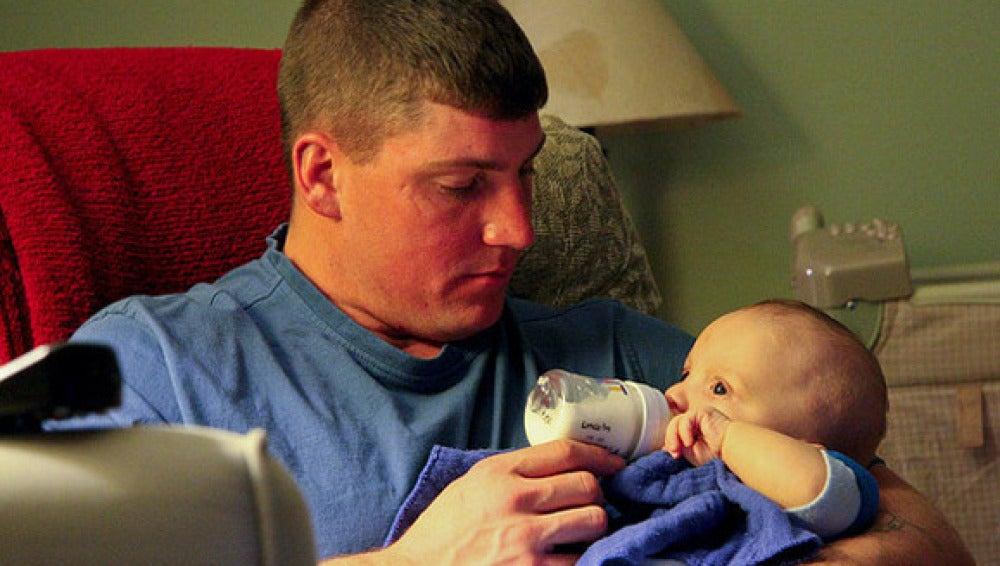 Un padre da el biberón a su hijo
