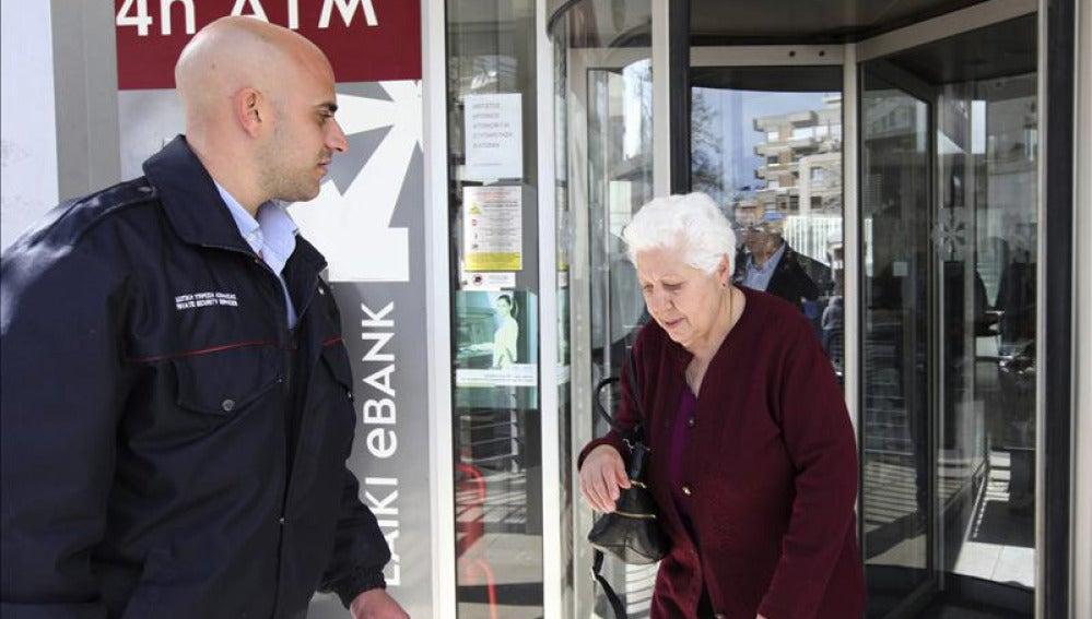 Una mujer sale de una sucursal de Laiki Bank, en Nicosia.