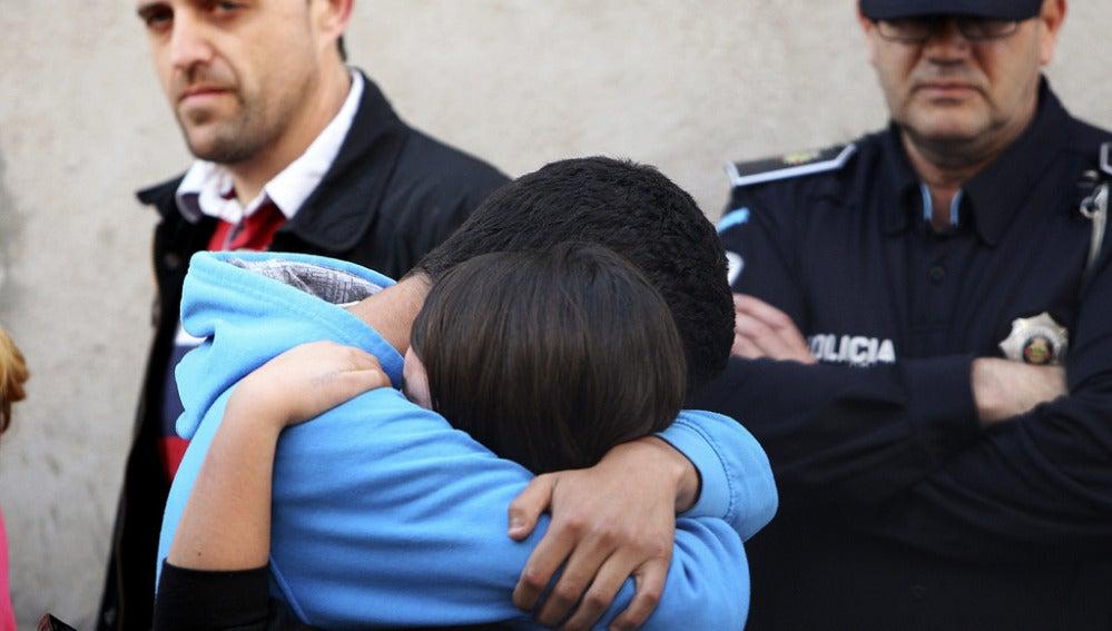 Familiares y amigos de las víctimas se abrazan a las afueras del domicilio