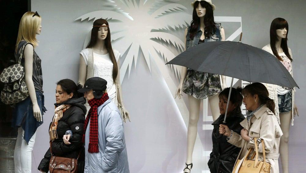 Varias mujeres se protegen de la lluvia y del frío registrado en Pamplona