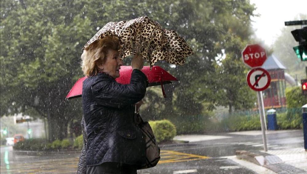 Una mujer se refugia del viento y la lluvia con el paraguas