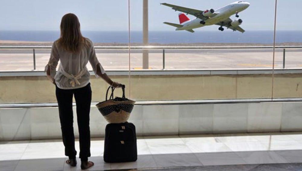 Una joven con su maleta espera en el aeropuerto