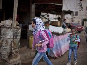 Dos niñas sirias que se dirigen a un colegio del distrito de Saif Al-Dawla, en Alepo (Siria)