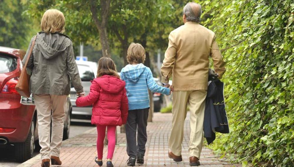 Unos abuelos acompañan a sus nietos al colegio.