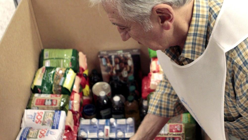 Un voluntario coloca alimentos en una caja