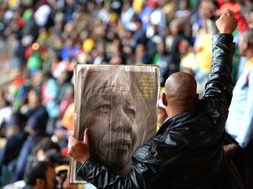 Un sudafricano porta una imagen de Mandela