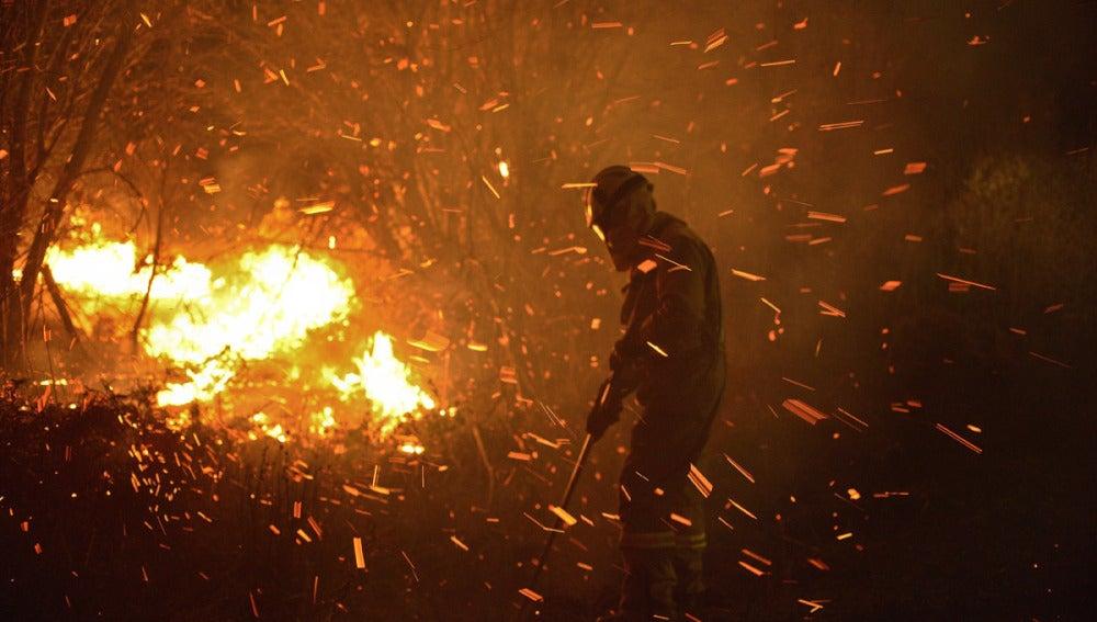 Un operario trabaja para apagar el fuego