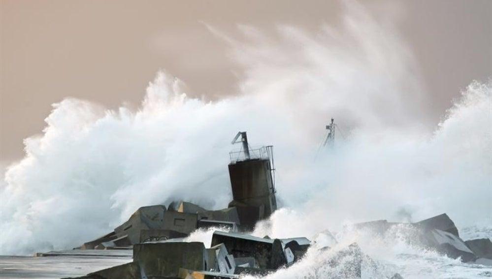Una ola rompe contra la costa en la playa de San Juan de Nieva en Avilés.