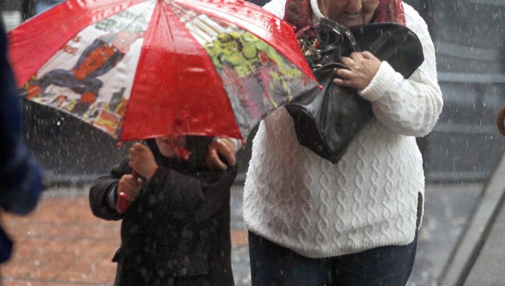 Una señora y un niño bajo la lluvia