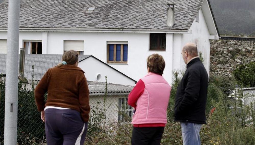 Varios vecinos de la zona observan la vivienda donde se produjo el crimen